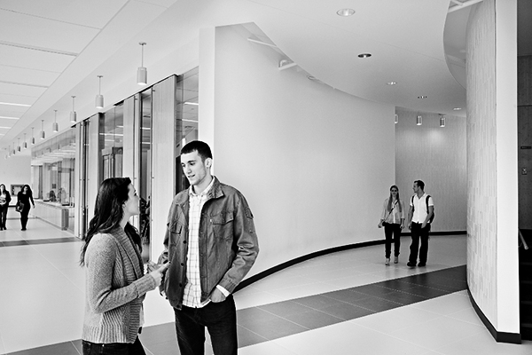black and white photo of two students talking in a hallway