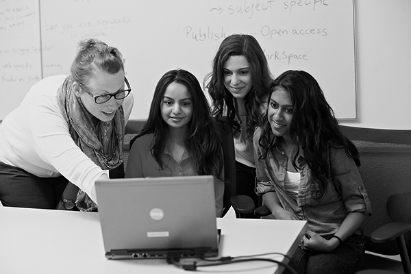 black and white photo of a group of students sitting around a laptop