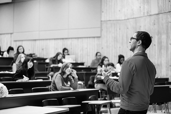 black and white photo of professor teaching in a lecture hall