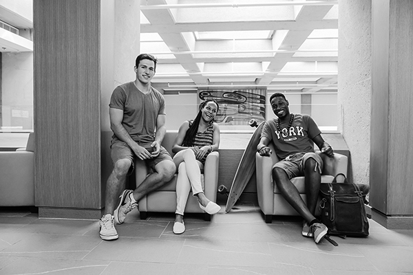 black and white photo of three students sitting in a hallway lounge