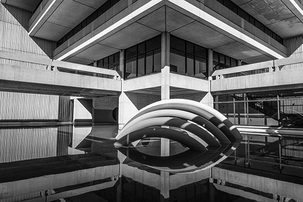 black and white photo of the rainbow sculpture behind Scott Library